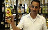 Illustration : Wilbert Wilson Rivero, un barman juif qui travaille à l'hôtel Raquel de La Havane, exhibe fièrement une bouteille de rhum Havana Club. (Larry Luxner/Times of Israel)