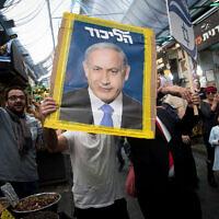 Un partisan du Likud tient une affiche de campagne montrant le Premier ministre  Benjamin Netanyahu sur le marché  Mahane Yehuda de Jérusalem, le 7 avril 2019 (Crédit : Yonatan Sindel/Flash90)