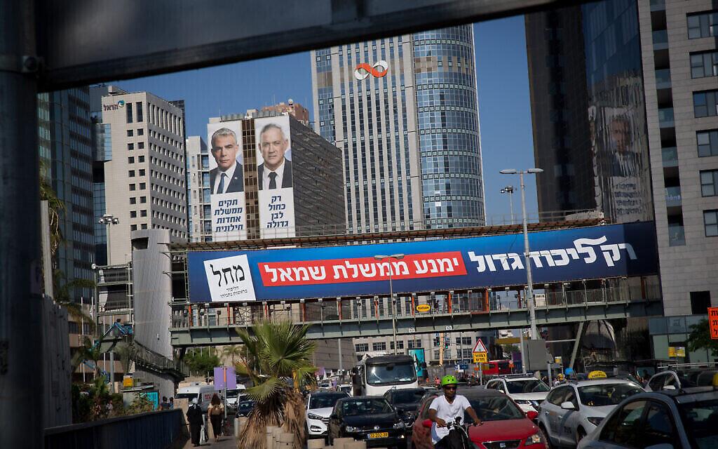 """Un panneau d'affichage portant la mention """"Seul un grand Likud empêchera un gouvernement de gauche"""", dans le cadre de la campagne électorale du Likud, vu près des affiches électorales des dirigeants du parti Kakhol lavan Yair Lapid et Benny Gantz, à Tel Aviv, le 11 septembre 2019. (Alster/Flash90)"""