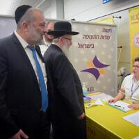 Le ministre de l'Intérieur Aryeh Deri, à gauche, et le ministre de la Santé  Yaakov Litzman rencontrent les personnels médicaux suite aux informations transmises sur le coronavirus meurtrier à l'aéroport international Ben-Gurion, le 2 février 2020 (Crédit : Avshalom Shoshani/Flash90)