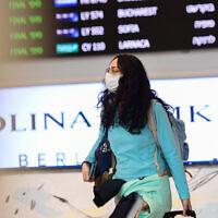 Les gens portent des masques à l'aéroport international Ben Gurionsuite à des informations sur le virus meurtrier apparu en Chine, qui s'est propagé dans le monde entier, le 17 février 2020 (Crédit :  Avshalom Shoshani/Flash90)