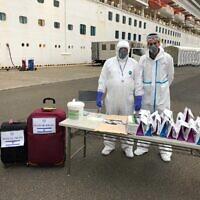 Des responsables portant des vêtements de protection attendent que les passagers israéliens quittent le navire de croisière Diamond Princess où ils ont passé deux semaines en quarantaine en raison d'une épidémie de coronavirus à bord, le 20 février 2020. (Crédit : Ambassade d'Israël à Tokyo)