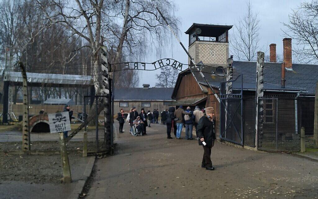 """Sol Graf franchit la fameuse porte sur laquelle on peut lire """"Arbeit Macht Frei"""", ou """"le travail rend libre"""", sur l'ancien site d'Auschwitz-Birkenau, le 28 janvier 2020. (Yaakov Schwartz/ Times of Israel)"""