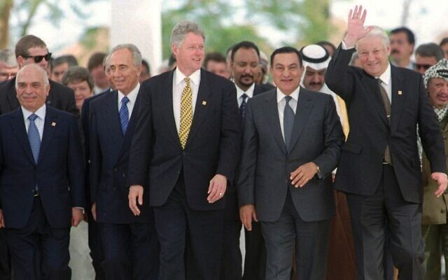 """Sur cette photo du 13 mars 1996, le président russe Boris Eltsine fait signe de la main alors que lui et (de gauche à droite) le roi Hussein de Jordanie, le Premier ministre israélien Shimon Pérès, le président américain Bill Clinton, le président égyptien Hosni Moubarak et, à l'extrême droite, le chef de l'OLP Yasser Arafat se dirigent vers la photo de groupe à la fin de leur sommet d'une journée des """"bâtisseurs de la paix"""" à Charm el-Cheikh, en Égypte. (AP Photo/Jerome Delay, File)"""