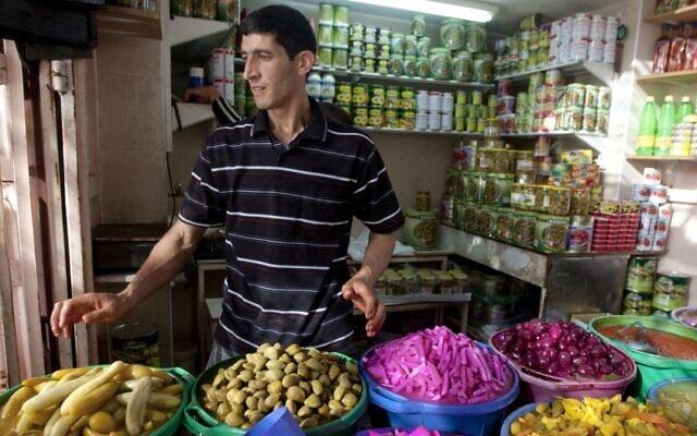 Un vendeur palestinien propose des produits alimentaires, notamment des légumes et des olives marinés, en préparation du Ramadan, sur un marché de la ville de Hébron, en Cisjordanie, le 28 juin 2014. (AP/Majdi Mohammed)