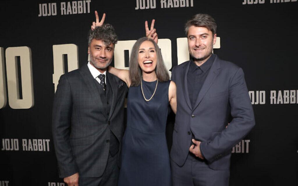 """De gauche à droite, le réalisateur et acteur Taika Wititi, la romancière Christine Leunens,et le producteur Carthew Neal lors de la première de """"Jojo rabbit"""" à Los Angeles (Crédit : Searchlight Pictures)"""
