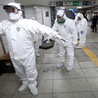 Des travailleurs portant leur tenue de protection aident à nettoyer leurs équipements respectifs après la désinfection contre le coronavirus dans une station du métro de Séoul, en Corée du Sud, le 21 février 2020. (Crédit : AP Photo/Ahn Young-joon)