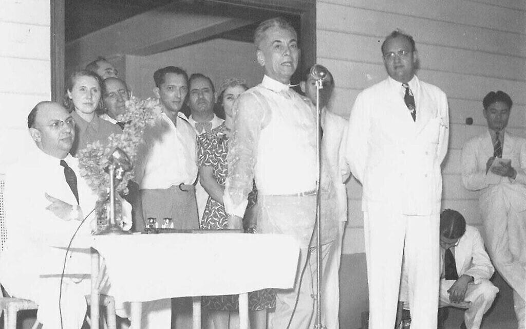 """Le président philippin Manuel L. Quezon (au centre au micro) accueillant des réfugiés juifs le 23 avril 1940 lors de l'inauguration du Marikina Hall, qu'il a construit sur sa propre propriété pour loger les immigrants nouvellement arrivés. À sa gauche se trouve Alex Frieder (costume blanc/assis), président du Comité des réfugiés juifs des Philippines, et à droite (costume blanc/assis) Herbert Frieder. (Avec l'aimable autorisation de """"Rescue in the Philippines"""")"""