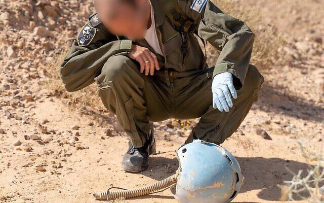 Un aviateur inspecte le casque d'un pilote israélien mort dans un accident d'avion dans le sud d'Israël en 1984, dans le désert de Paran en février 2020. (Crédit : armée israélienne)