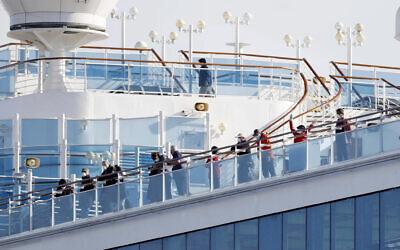 Des passagers sont sur le pont du bateau de croisière Diamond Princess amarré dans le port de Yokohama à Yokohama, non loin de Tokyo, le mercredi 12 février 2020. (Yuta Omori/Kyodo News via AP)