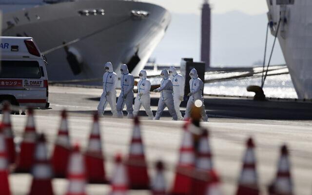 Du personnel médical en tenue de protection s'éloigne du bateau de croisière Diamond Princess placé en quarantaine à Yokohama, à proximité de Tokyo, le mardi 11 février 2020. (AP Photo/Jae C. Hong)
