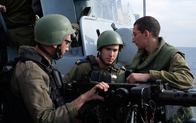 Des marins israéliens se préparent à tirer avec une mitrailleuse lors d'un exercice de la marine au large de la côte nord de la ville israélienne d'Haïfa, le 3 février 2020. (Judah Ari Gross/Times of Israël)