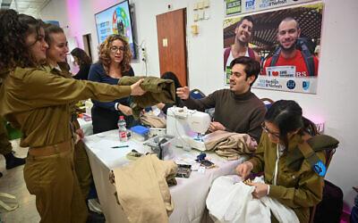 """Un soldat seul de Tsahal tend à un tailleur une paire de pantalon lors de l'événement annuel """"Jour de Commissions"""" à Tel Aviv, le 13 février 2020.  (Shahar Azran/Nefesh B'Nefesh)"""