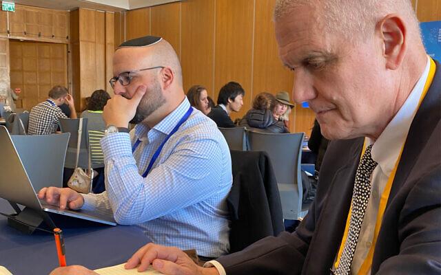 Will Irwin, à droite, à une conférence OurCrowd à Jérusalem écrivant son nom, le 13 février 2020. (Shoshanna Solomon / Times of Israël)
