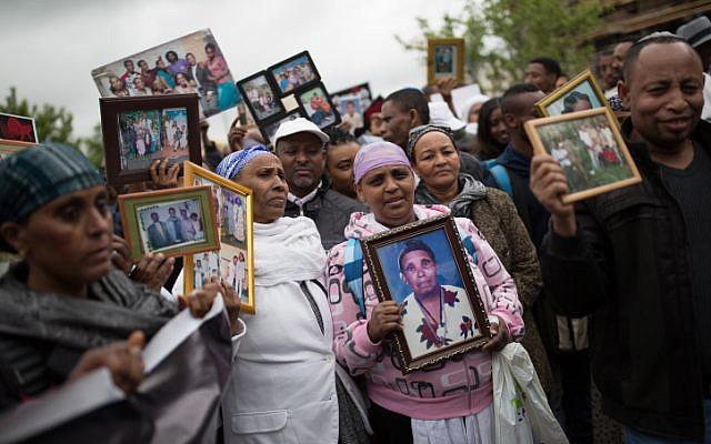 Des Israéliens qui ont immigré d'Ethiopie montrent des photos de famille de leurs proches restés en Ethiopie, lors d'une manifestation à Jérusalem pour faire venir le reste des Falashmura, le 20 mars 2016. (Corinna Kern/Flash90)