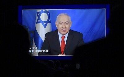 Le Premier ministre Benjamin Netanyahu s'exprime depuis Israël via vidéo lors de la conférence annuelle de l'AIPAC à Washington, le 26 mars 2019 (Crédit :   Jim Watson/AFP)