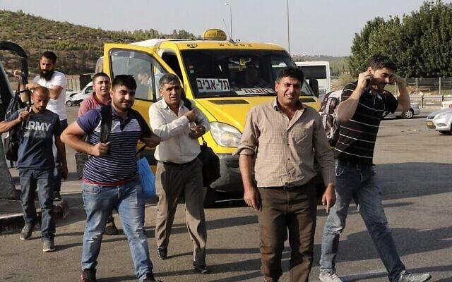 Une photo prise du côté israélien du poste de contrôle de Tarkumiya, près de la ville de Kiryat Gat, dans le sud du pays, montre des travailleurs palestiniens qui pénètrent en Israël pour rejoindre leur lieu de travail, le 14 novembre 2019. (HAZEM BADER / AFP)