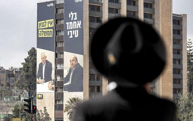 """Un homme ultra-orthodoxe passe près d'un panneau d'affichage du Likud pour les prochaines élections générales en Israël, le 17 février 2020, montrant les portraits (de gauche à droite) du général à la retraite Benny Gantz, chef de l'alliance politique Kakhol lavan et d'Ahmad Tibi, membre de la Knesset pour la Liste arabe unie, avec une légende qui dit : """"Gantz n'a pas de gouvernement sans Tibi"""". (Ahmad Gharabli/AFP)"""