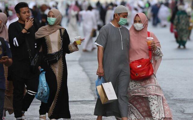 Les pèlerins musulmans portent des masques à la grande mosquée de la ville de la Mecque, en Arabie saoudite, le 28 février 2020 (Crédit : Abdel Ghani Bashir/AFP)