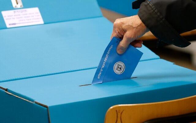 Un bulletin de vote glissé dans l'urne lors des élections nationales du 2 mars 2020. (Crédit : Emmanuel DUNAND / AFP)