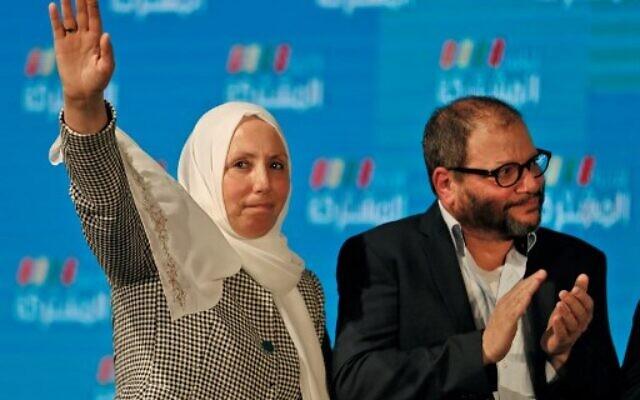 Iman Khatib Yassin, politicienne israélo-arabe représentant la branche sud du Mouvement islamique au sein de l'alliance électorale de la Liste arabeb unie, à côté d'Ofer Cassif, membre juif et candidat du parti Hadash au sein de l'alliance, devant des partisans à leur siège électoral dans la ville de Shefa-Amr, au nord d'Israël, le 2 mars 2020, après la fermeture officielle des bureaux de vote. (Crédit : Ahmad GHARABLI / AFP)