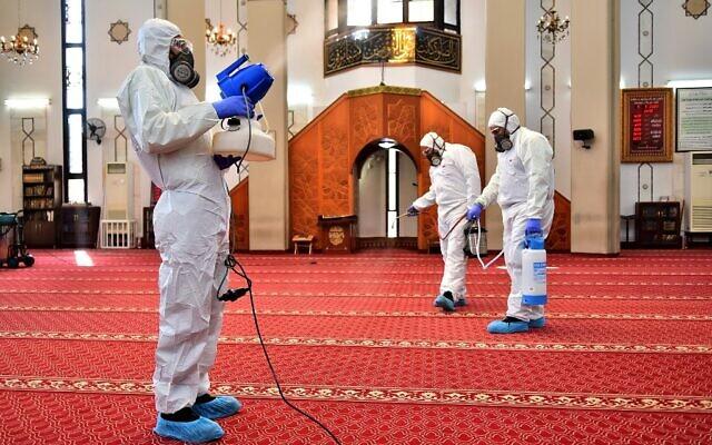 Des employés des services sanitaires désinfectent une mosquée à Beyrouth, le 5 mars 2020.  (Photo par - / AFP)