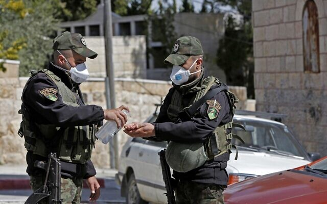 Des forces de sécurité palestiniennes portant des masques se désinfectent les mains à côté d'un hôtel qui a été bouclé dans la ville de Beit Jala suite à des cas suspects de coronavirus COVID-19, le 5 mars 2020. (Crédit : Musa Al SHAER / AFP)
