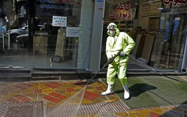 Des pompiers iraniens et des employés municipaux désinfectent une rue de la capitale Téhéran pour le COVID-19 le 5 mars 2020. (Crédit : STR / AFP)