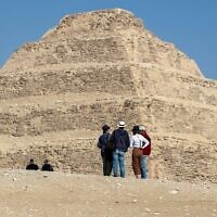 Des visiteurs observent la pyramide de Djoser dans la nécropole égyptienne de Saqqara, au sud de la capitale du Caire, le 5 mars 2020. (Photo par Mohamed el-Shahed / AFP)