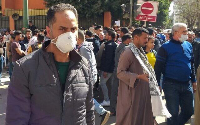 Des Égyptiens se rassemblent dans le centre-ville du Caire en attendant de se faire tester pour le coronavirus, le 8 mars 2020. (Khaled DESOUKI / AFP)