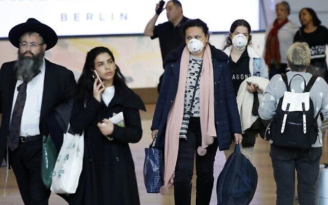 Des passagers portant des masques de protection dans le hall d'arrivées de l'aéroport international Ben Gurion près de Tel Aviv, le 10 mars 2020. (Crédit : Jack Guez/AFP)
