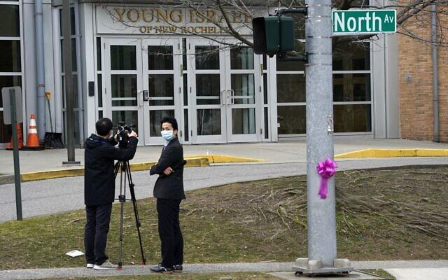 Des médias portant un masque de protection devant la synagogue Young Israel of New Rochelle, à New York, le 10 mars 2020, au centre d'une épidémie dans le comté de Westchester (Crédit : TIMOTHY A. CLARY / AFP)