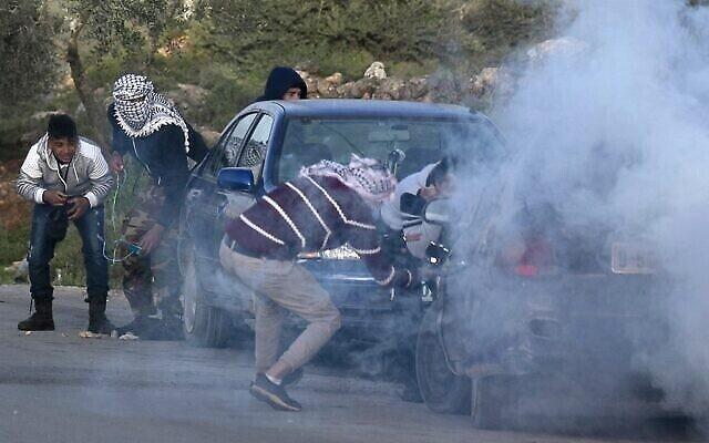 De jeunes Palestiniens se protègent contre des gaz lacrymogènes lors de heurts avec les forces israéliennes dans un village au sud de Naplouse en Cisjordanie, le 11 mars 2020. (Crédit : JAAFAR ASHTIYEH / AFP)
