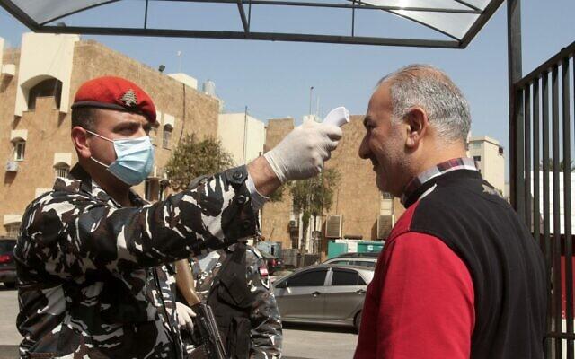 Un membre de la sécurité libanaise vérifie la température d'un visiteur à l'entrée du Sérail gouvernement dans la ville du sud de Saida, le 11 mars 2020, par prévention contre la nouvelle épidémie de coronavirus. (Photo par Mahmoud ZAYYAT / AFP)