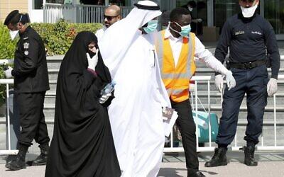 La police qatari se trouve devant un hôtel à Doha alors qu'un soignant accompagne des personnes portant des masques par crainte du coronavirus, le 12 mars 2020. (Photo par - / AFP) / Qatar OUT)