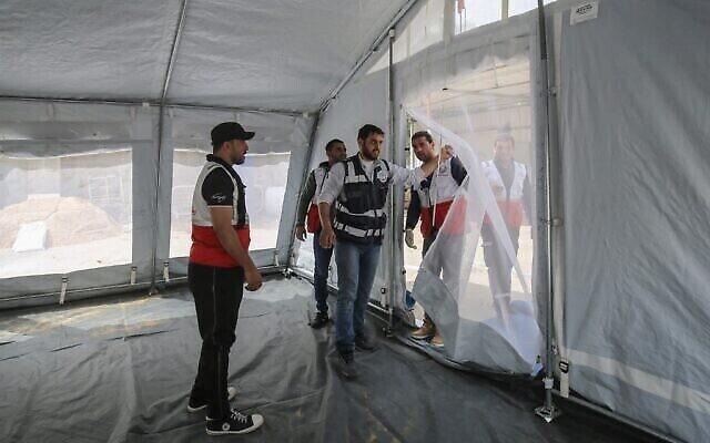 Des membres du ministère palestinien de la Santé, en partenariat avec l'Organisation mondiale de la santé (OMS), installent des tentes extérieures pour un examen médical préliminaire des patients suspectés d'être porteurs du coronavirus au poste-frontière de Rafah avec l'Égypte, dans le sud de la bande de Gaza, le 12 mars 2020. (Crédit : SAID KHATIB / AFP)