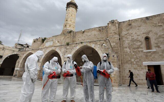 Des travailleurs palestiniens portant des équipements de protection se préparent à désinfecter les murs de la mosquée al-Omari, en prévention de la propagation du coronavirus COVID-19, dans la ville de Gaza, le 12 mars 2020. (Crédit : MAHMUD HAMS / AFP)