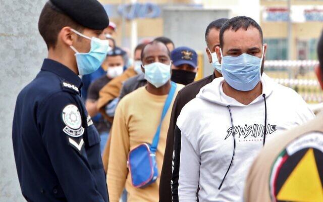 Des travailleurs expatriés de retour d'Egypte, de Syrie et du Liban arrivent au ministère de la Santé, dans la zone de confinement et de contrôle en pleine pandémie du COVID-19, à Koweït City, le 15 mars 2020 (Crédit :  YASSER AL-ZAYYAT / AFP)