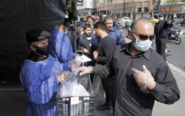 Des personnes font la queue pour recevoir des paquets pour lutter contre la coronavirus COVID-19 fournis pa le Basijj, une milice loyale aux autorités de la République islamique d'Iran, dans des stands devant la station de métro Meydane Valiasr dans la capitale Téhéran le 15 mars 2020. - (Photo par STRINGER / AFP)