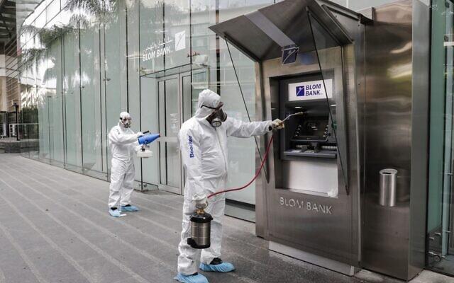 Des employés d'une société privée désinfectent un guiche de banque,   pour limiter la propagation du coronavirus, à Beyrouth, au Liban, le 15 mars 2020. (Crédit : ANWAR AMRO / AFP)