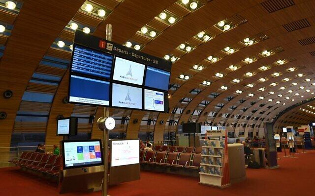Un écran d'affichage avec des conseils sur le coronavirus dans la zone d'embarquement vide de l'aéroport Charles de Gaulle à Paris, le 15 mars 2020. (Crédit : Roslan Rahman / AFP)