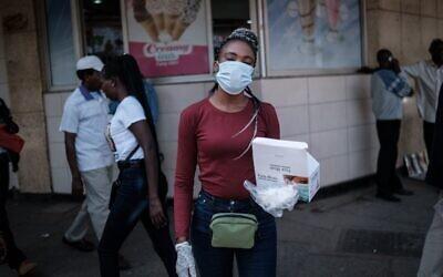 Une femme vend des masques pour environ 2 dollars l'unité dans une rue du centre-ville de Nairobi, au Kenya, le 16 mars 2020. (Photo par Yasuyoshi CHIBA / AFP)