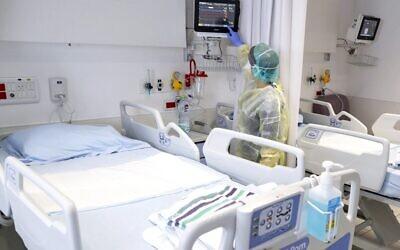 La directrice du service des épidémies, le Dr Karina Glick, vérifie un moniteur des signes vitaux d'un patient dans un service, tout en portant des vêtements de protection, lors d'une présentation à la presse du service d'hospitalisation des futurs patients atteints de coronavirus à l'hôpital universitaire Samson Assuta Ashdod, le 16 mars 2020, dans la ville d'Ashdod, au sud d'Israël. (JACK GUEZ / AFP)/
