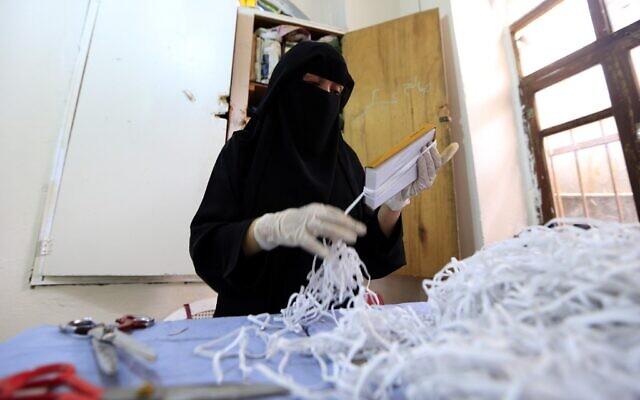 Une femme yéménite fabrique des masques dans une usine textile de la capitale Sanaa, le 16 mars 2020, en pleine pandémie de coronavirus. (Crédit :  Mohammed HUWAIS / AFP)