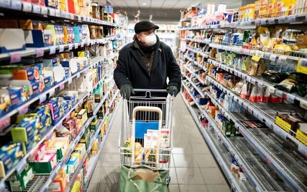 Un homme portant un masque facial, porté par beaucoup comme mesure de protection contre le nouveau coronavirus COVID-19, pousse un caddie dans un supermarché de Berlin le 17 mars 2020. (Kay Nietfeld / dpa / AFP)