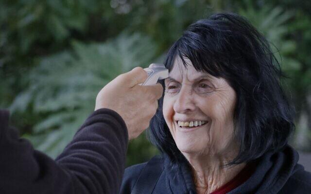 Un agent de sécurité israélien mesure la température d'une femme à l'entrée d'une maison de retraite dans le quartier de Ramat Efal à Ramat Gan en Israël, le 17 mars 2020. (PJACK GUEZ / AFP)