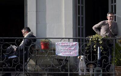 """Deux hommes se tiennent sur leur balcon avec une banderole portant l'inscription """"Restez chez vous"""", à Nantes, le 17 mars 2020, alors qu'un confinement strict entre en vigueur pour arrêter la propagation de la COVID-19 en France. (Crédit : Sébastien SALOM-GOMIS / AFP)"""