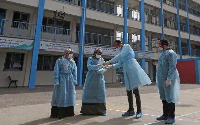 Des soignants palestiniens portent des masques de protection et se préparent à soigner et isoler des patients du coronavirus, dans la cour d'une école de l'UNRWA, à Gaza, le 18 mars 2020. (Crédit : MAHMUD HAMS / AFP)