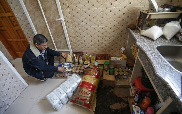 Mustafa al-Khatib, un Palestinien de 51 ans, trie des denrées alimentaires dans la cuisine de sa maison à Gaza City, le 18 mars 2020, en pleine pandémie de coronavirus. (Crédit :  Mohammed ABED / AFP)