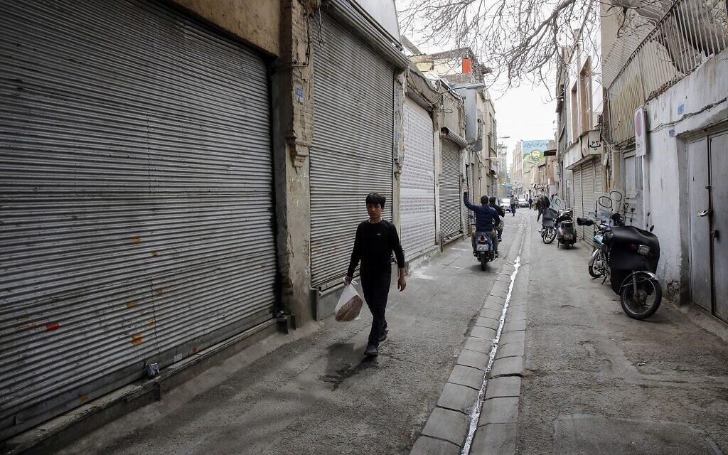 Des jeunes iraniens passent à côté de boutiques fermées dans le grand bazaar de la capitale Téhéran pendant la crise du coronavirus, le 18 mars 2020. (Photo par - / AFP)